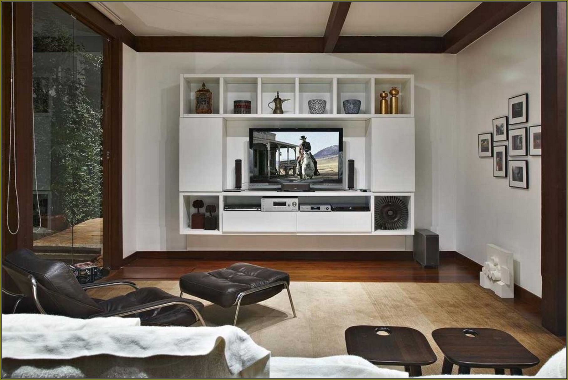 Popular Hidden Tv Units Inside White Wooden Shelves With Tv On The Middle Placed On The White (View 13 of 15)